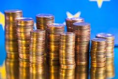 Sluit omhoog van euro muntstukken op blauwe achtergrond stock foto