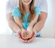 Sluit omhoog van familiehanden houdend euro geldmuntstukken Stock Foto's