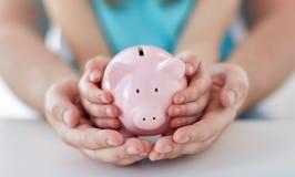 Sluit omhoog van familiehanden met spaarvarken Royalty-vrije Stock Foto