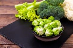 Sluit omhoog van geassorteerde gezonde verse groenten op een zwarte lei op een houten lijst: kool, broccoli, bloemkool en Royalty-vrije Stock Fotografie