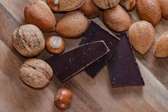 Sluit omhoog van geassorteerde noten en pices van chocolade op een houten lusje royalty-vrije stock afbeelding