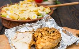 Sluit omhoog van gebakken kippenborst op folie en het grote verstand van de kleischotel Stock Afbeeldingen