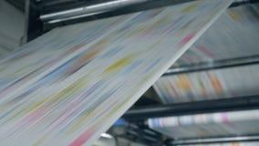 Sluit omhoog van gekleurd document die zich door de fabriekspers bewegen stock video