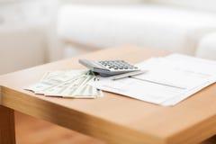 Sluit omhoog van geld en calculator op lijst thuis Stock Foto's