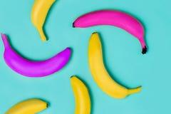 Sluit omhoog van gele, roze en purpere bananen op een bed blauwe achtergrond royalty-vrije stock fotografie