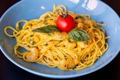 Sluit omhoog van gele spaghetti met garnalen, een kersentomaat en een basilicum royalty-vrije stock afbeeldingen