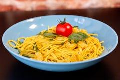 Sluit omhoog van gele spaghetti met garnalen, een kersentomaat en een basilicum in een blauwe plaat op een zwarte lijst royalty-vrije stock foto's