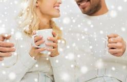 Sluit omhoog van gelukkig paar met theekoppen thuis Royalty-vrije Stock Afbeeldingen