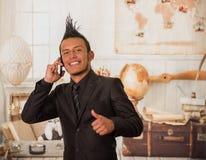 Sluit omhoog van gelukkige bureau punkarbeider die een kostuum met een kam dragen, gebruikend zijn cellphone in het bureau in vaa Royalty-vrije Stock Foto's