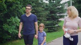 Sluit omhoog van gelukkige familie die samen op straat het lachen lopen Vader en moeder die aan elkaar en zoon spreken stock videobeelden