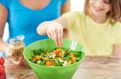 Sluit omhoog van gelukkige familie kokende salade in keuken Stock Foto