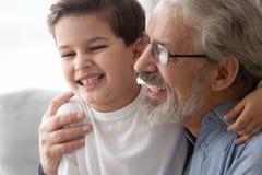 Sluit omhoog van gelukkige grootouderomhelzing die pret met kleinkind hebben royalty-vrije stock foto
