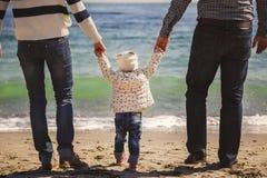 Sluit omhoog van gelukkige houdende van familie die met klein jong geitje in het midden, bij strand samen dichtbij de oceaan lope royalty-vrije stock afbeelding