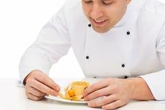 Sluit omhoog van gelukkige mannelijke chef-kokkok die dessert verfraaien Stock Afbeelding