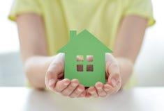 Sluit omhoog van gelukkige meisjeshanden houdend document huis Stock Foto's