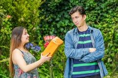 Sluit omhoog van gelukkige vrouw een gift en bloemen houden die bekijkend zijn verbrijzeling en jongen met zijn gekruiste wapens  stock afbeeldingen