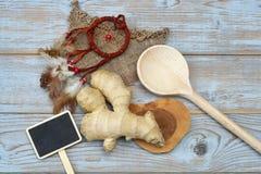Sluit omhoog van gemberwortel op oude houten plankenachtergrond met houten lepel en bordmarkering met lege exemplaarruimte Stock Fotografie