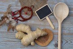 Sluit omhoog van gemberwortel op oude houten plankenachtergrond met houten lepel en bordmarkering met lege exemplaarruimte Royalty-vrije Stock Fotografie