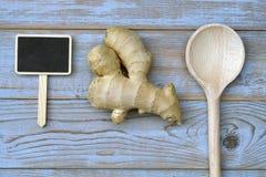 Sluit omhoog van gemberwortel op oude houten plankenachtergrond met houten lepel en bordmarkering met lege exemplaarruimte Royalty-vrije Stock Foto