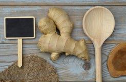 Sluit omhoog van gemberwortel op oude houten plankenachtergrond met houten lepel en bordmarkering met lege exemplaarruimte Royalty-vrije Stock Foto's
