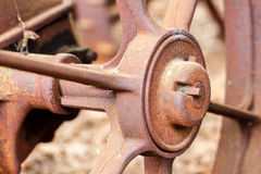 Sluit omhoog van geroest wiel op verlaten landbouwbedrijfmateriaal royalty-vrije stock afbeeldingen
