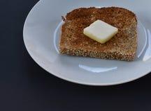 Sluit omhoog van geroosterd sesamzaad ontsproten korrelbrood en botervierkant op witte plaat en zwarte achtergrond Royalty-vrije Stock Foto's