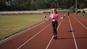 Sluit omhoog van geschiktheid-vrouw voeten springend, gebruikend touwtjespringen in stadion stock footage