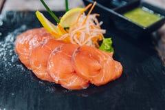 Sluit omhoog van Gesneden ruwe die zalm als voorgerecht wordt gediend Gediend met Thaise kruidige saus stock afbeeldingen