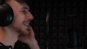 Sluit omhoog van gezicht van jong het glimlachen jongen het zingen lied aan microfoon Portret van de Kaukasische mens in hoofdtel stock video