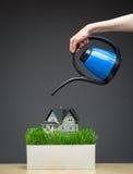 Sluit omhoog van gietend het huismodel van de waterpot met gras Stock Fotografie