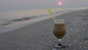 Sluit omhoog van glas van fruitcocktail op een tropisch strand bij zonsondergang in de avond stock footage