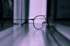 Sluit omhoog van glazen leggend op een lijst voor een open boek stock afbeelding