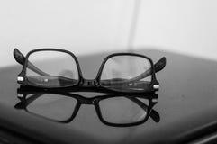 Sluit omhoog van glazen op laptop op het bureau worden geplaatst dat Stock Foto