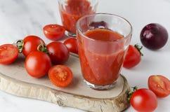 Sluit omhoog van glazen van vers gedrukt tomatesap, ruwe kersentomaten en ui op houten raad royalty-vrije stock foto's
