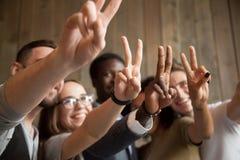 Sluit omhoog van glimlachende diverse mensen die vredesteken tonen royalty-vrije stock afbeeldingen