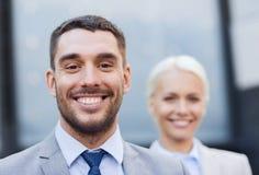 Sluit omhoog van glimlachende zakenlieden Stock Foto's