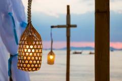 Sluit omhoog van gloeilamp op de draad Gloed omhoog in de lamp Hangend op het strand, tegen de zonsonderganghemel en andere lamp  stock fotografie
