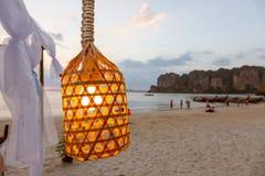 Sluit omhoog van gloeilamp op de draad Gloed omhoog in de lamp Het hangen op het strand tegen de achtergrond van toeristen die op royalty-vrije stock foto