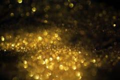 Sluit omhoog van Gouden poeder met schitteren lichten op zwarte achtergrond royalty-vrije illustratie