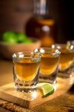 Sluit omhoog van gouden Tequila-schotenvlucht met gesneden kalk en zout royalty-vrije stock foto
