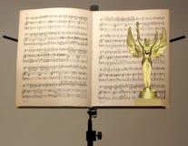 Sluit omhoog van gouden trofee en muzieknotatribune royalty-vrije stock afbeeldingen