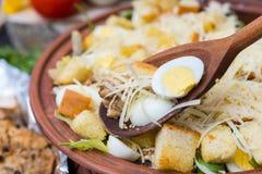 Sluit omhoog van grote kleischotel met smakelijke caesar salade met een woode Stock Fotografie