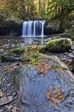 Sluit omhoog van grote rotsen in voorgrond met waterval royalty-vrije stock afbeelding