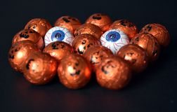 Sluit omhoog van Halloween-hefboom-o-Lantaarn folie behandelde snoepjes Stock Fotografie