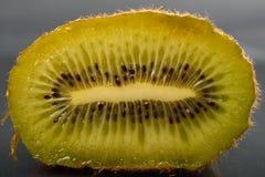 Sluit omhoog van halve kiwi met verschrompelde huid bij de donkere bezinning backg Royalty-vrije Stock Afbeelding