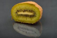 Sluit omhoog van halve kiwi met verschrompelde huid bij de donkere bezinning backg Stock Afbeeldingen