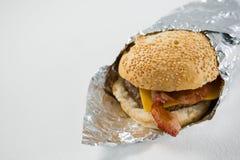 Sluit omhoog van hamburger in foliedocument dat wordt verpakt Royalty-vrije Stock Foto's