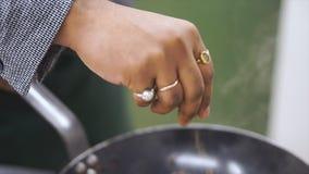 Sluit omhoog van hand van Chef-kok die kruiden op schotel in keuken bestrooien klem De chef-kok bereidt de schotel voor Bestrooi  royalty-vrije stock foto