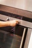 Sluit omhoog van Hand het Draaien Knop op Oven stock afbeelding