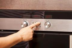 Sluit omhoog van Hand het Draaien Knop op Oven royalty-vrije stock foto's